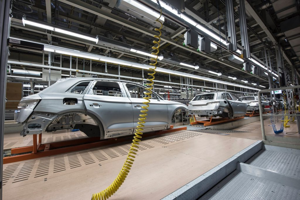 Auto assembly line with unfinished cars that demonstrates business process workflow