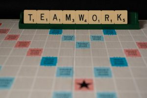 Scrable board that spells TEAMWORK for smoothly updating supplier specifications
